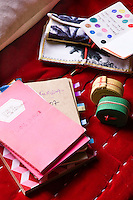 A collection of notebooks on a red velvet stool