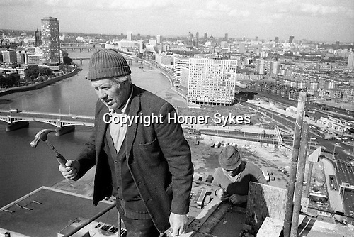 Irish laborers construction workers holding hammer at the top of and working on a Nine Elms tower block. London skyline and River Thames  and the House of Parliament. England 1974