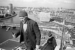 Irish labourers construction workers holding hammer at the top of and working on a Nine Elms tower block. London skyline and River Thames  and the House of Parliament. England 1974