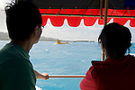 Chinese tourists look out at the yellow submarine Deepstar in Saipan..Photographer: Robert Gilhooly