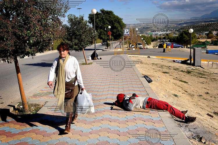 A woman walks past an illegal migrant sleeping at the roadside. Many of migrants come to the region to pick olives but this year there is competition for the work. The economic collapse means that work once shunned by the indigenous population is now sought after by unemployed Spaniards.