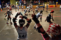 Maura Buse cheers her teammates on during a roller derby bout in Wilmington, Massachusetts. Roller derby is an American contact sport, popular with young women, which combines both athleticism and a satirical punk third-wave feminism aesthetic.