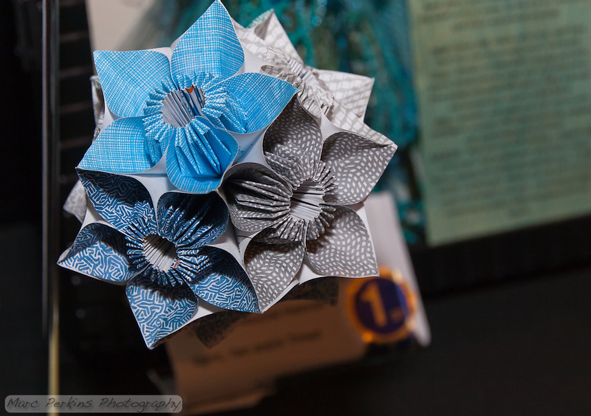 "Michelle won first place  at the 2011 OC Fair for a kusudama (ball origami) project made from recycled security envelopes.  This is a closeup of her project, where you can see the different security envelope patterns she used.  Each individual unit of each flower was folded from a 4""x4"" square of paper cut out from a security envelope we'd received in the mail."