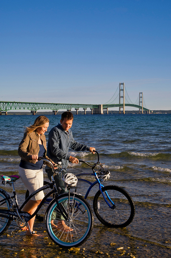 A couple walks their bikes along a beach with a view of the Mackinac Bridge in Mackinaw City, Michigan.
