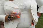 Woman with false long orange nails, spilt drink on white suit dress. The Derby horse race. Epsom Down Surrey UK. 2012