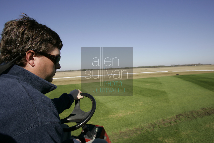 Pennington seed agronomist Russ Nicholson (cq) shows a section of turf at Jennings Turf Farms in Riddleville, Ga. on Thursday, Dec. 28, 2006. About 100,000 square feet of the turf will be trucked to Miami to be used for the Super Bowl game.