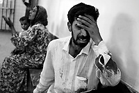 Baghdad, Iraq, April 5, 2003.Rahad Salman, 23, in the Al Kindi hospital emergency ward cries and prays for the life of his son Mustapha Odei, 4, eviscerated and criticaly injured by shrapnel in the head, at Ubeidi by a US bomb. According to the doctors in attendance Mustapha has no chance to survive. More than 70 US bombardment victims were admitted in less than 2 hours after a B52 carpet bombing on the Northern outskirts, about a fifth of these were military personel.