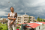 Ms. Aruna Awale-Meteorologist for the Alternative Energy Promotion Center in Kathmandu poses for a picture. In the background is a wind turbine provided by MEC.
