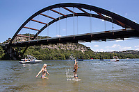 Austin locals in bikinis enjoy swimming in the cool waters of Lake Austin at the Loop 360 Bridge Park in west Austin, Texas.