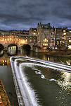 Pulteney Bridge in Bath, Somerset, England at night with glowing lights and stormy sky