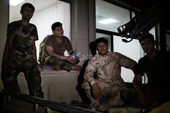KIRKUK, IRAQ: Peshmerga relax, exchanging stories about a recent battle, in the evening at Maktabi Khalid Peshmerga base on the outskirts of Kirkuk.<br /> <br /> Peshmerga are the Kurdish military forces. Those based at Maktabi Khalid play both support and combat roles in the conflict with Sunni militants led by the Islamic State of Iraq and al-Sham, who recently took all but 50km of the territory that borders the semi-autonomous region of Iraq Kurdistan.<br /> <br /> Credit: Hawre Khalid/Metrography