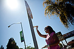 Sharde Santini paints a stop sign post in Stockton, Calif., July 11, 2012. The bankrupt city has cut back on many services, while residents and private contractors are picking up the slack.