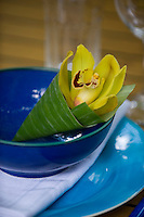A yellow orchid wrapped in a banana leaf in a blue bowl