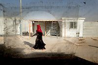A woman walks along a road at the Zaatari Refugee Camp. Approximately two million people have fled the conflict in Syria. At least 130,000 of them live in Zaatari Refugee Camp, although it was designed to house 60,000, and a further 2,000 people arrive each day.