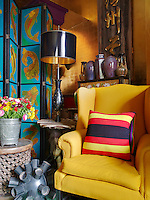 One corner of the living room is filled with a bright yellow wing-backed armchair and a hand-painted screen