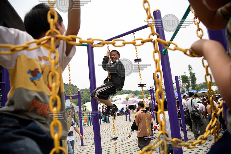 Children play at a temporary shelter at the Jiuzhou Stadium in Mianyang. On the 12/05/2008 an earthquake measuring 8.0 on the Richter scale hit the province of Sichuan.