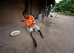 "Gota Dzongololo, 11, eats sorghum porridge in the morning after getting dressed in his school uniform. He lives in Chidyamanga, a village in southern Malawi that has been hard hit by drought in recent years, leading to chronic food insecurity, especially during the ""hunger season,"" when farmers are waiting for the harvest."