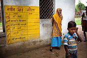 A old woman is seen standing next to the weekly mid-day meal menu on the school wall in village Karhai outside of Jhansi, Uttar Pradesh, India. The Indian government spends $1.4 billion a year - on programs that include weighing newborn babies, counseling mothers on healthy eating and supplementing meals, but none of this is yeilding results. According to UNICEF, some 48% of Indian children, or 61 million kids, remain malnourished, the clinical condition of being so undernourished that their physical and mental growth are stunted. Photo: Sanjit Das/Panos for The Wall Street Journal.Slug: IMALNUT