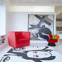 A red armchair by Les Migrateurs and a chair by AI Friedman surround a rug by RIchard Philips for the Art Production Fund