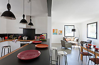 The open plan kitchen is separated from the living area by a free-standing kitchen island illuminated by a row of industrial style pendant lights