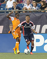 New England Revolution midfielder Diego Fagundez (14) asseses situation and dribbles as Houston Dynamo midfielder Boniek Garcia (27) closes. In a Major League Soccer (MLS) match, Houston Dynamo (orange) defeated the New England Revolution (blue), 2-1, at Gillette Stadium on July 13, 2013.