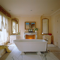 A pair of gilt-framed mirrors above the wash basins flank the marble fireplace in this sumptuous bathroom