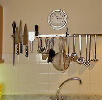 An impressive array of knives and stainless steel kitchen utensils hangs from a rail above the sink