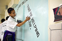 Jasmine Johnson, an eleven year old middle school student paints a mural against hate at a middle school in the borough of Brooklyn in New York on Sunday, March 25, 2012.  The mural was part of the Anti-Defamation League No Place for Hate program.  (© Frances M. Roberts)