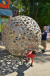 "Huntington, New York, U.S. 24th August 2013. A young boy is stepping out of a rolling metal sculpture ""Sphere of Hope"" which his father is still in, at the art event ""Off the Walls"" Block Party, by SPARKBOOM, a Huntington Arts Council project created to help emerging artists, showcase talents, and help its artistic family network. The sculpture is by sculpture Steven Zaluski, and is created from human shapes welded together."