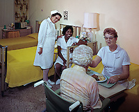 Nurse feeds old woman while two nurses watch.