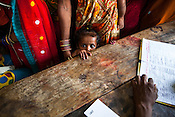 Caretakers and family workers gather to have their children checked during a mass screening at the local health centre in Inarwa in Saptari, Nepal.
