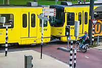 Nederland, Utrecht, 20 okt 2014<br /> Tram van openbaar vervoer in Utrecht op een kruising. Moeder met kind op fiets wacht tot ze kan oversteken. <br /> Foto: (c) Michiel Wijnbergh