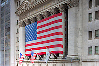 The neoclassical New York Stock Exchange on Wall Street displaying a large American flag.