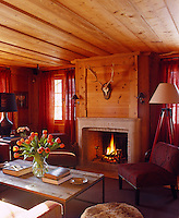 The cosy study has a roaring fire and thick red curtains for warmth