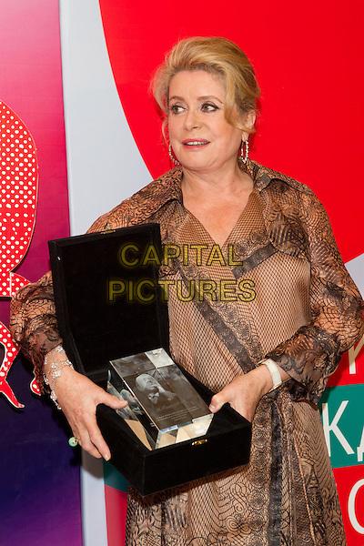 "Catherine Deneuve .Closing of the 34th MMKF. Deneuve won a prize I ""Trust"". Cinema ""October"", Moscow, Russia..June 30th, 2012.half length dress award trophy winner beige black print .CAP/PER/SB.©SB/PersonaStars/CapitalPictures"