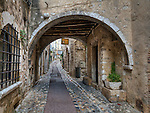 "View of archway and street (the Rue Grande), Saint Paul de Vence, showing the underside of the ""pontis"", or bridge, connecting buildings on opposite sides of the street."