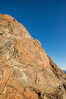 Female climber climbing pitch 2 on Reka mountain peak, Vesterålen, Norway