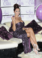 Amy Childs.The photocall to launch her debut fragrance in collaboration with Jigsaw, Aura bar & nightclub, London, England..August 15th, 2012.full length purple strapless dress slit split sequins sequined hair up bun sofa couch sitting silver sandals shoes legs crossed .CAP/CAN.©Can Nguyen/Capital Pictures.