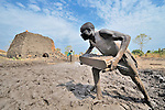 Men form mud into blocks that will be fired into bricks outside Minyori, a small village in Central Equatoria State in Southern Sudan.