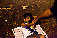 Razia Shabnam assists a child with sit-ups while she conducts a training session in Biyam Samiti park with children from the area of Kidderpore, Calcutta, West Bengal, India. Razia Shabnam, 28, was one of the first women boxers in Kolkata. She was also the first woman in her community to go to college. She is now a coach and one of only three international female boxing referees in India.  Photo by Suzanne Lee for Panos London