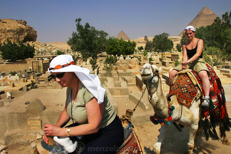 Tourists riding camels through the cemetery by the Pyramids at Giza, outside Cairo, Egypt.