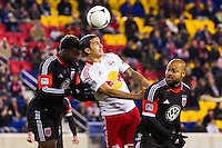 Brandon McDonald (4) and Robbie Russell (3) of D. C. United battle Tim Cahill (17) of the New York Red Bulls on a header. D. C. United defeated the New York Red Bulls 1-0 (2-1 in aggregate) during the second leg of the MLS Eastern Conference Semifinals at Red Bull Arena in Harrison, NJ, on November 8, 2012.