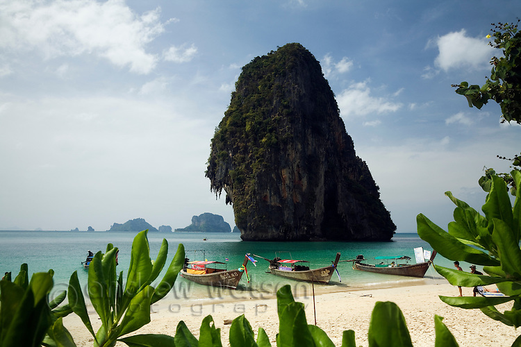 Longtail boats sit in the clear waters and karst scenery of Hat Phra Nang (Phra Nang Beach).  Railay, Krabi, THAILAND