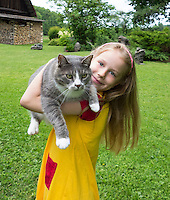 Happy smiling girl, childhood. Child holding cat. Yard, homestead in Estonia.