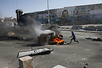 Palestinian protester throw a tire to the fire during clashes with Israel Defense Forces after the funeral held for three Palestinians killed during IDF operation at Kalandia refugee camp on August 26, 2013 in Ramallah, West Bank. Photo by Oren Nahshon