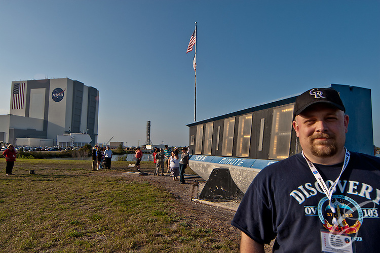 "NASA ""Tweetup"" participant Nicholas Roznovsky - aka the ""modernishfather"" poses with the exhaust trail of the Space Shuttle Discovery. Discovery took off from the Kennedy Space Center for the final time on February 24, 2011."