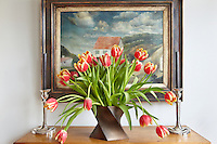 An arrangement of tulips in a ceramic vase by Jan van der Vaart partly conceals a painting by the Dutch artist Carel Willink, 1930