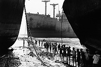 India. Province of Gujarat. Alang. Workers, all men, carry a wire to draw by winch a huge scrap's piece on the beach. Ships aground. Vessels stranded. Bottoms of ships at low tide on the shore. Alang, located in the Gulf of Khambhat, is a ships breaking place and is a ships breaking place. Alang is considered as the biggest scrapyard in the world. Ships recycling for its metals. Environmental issues. Hazardous waste. © 1992 Didier Ruef