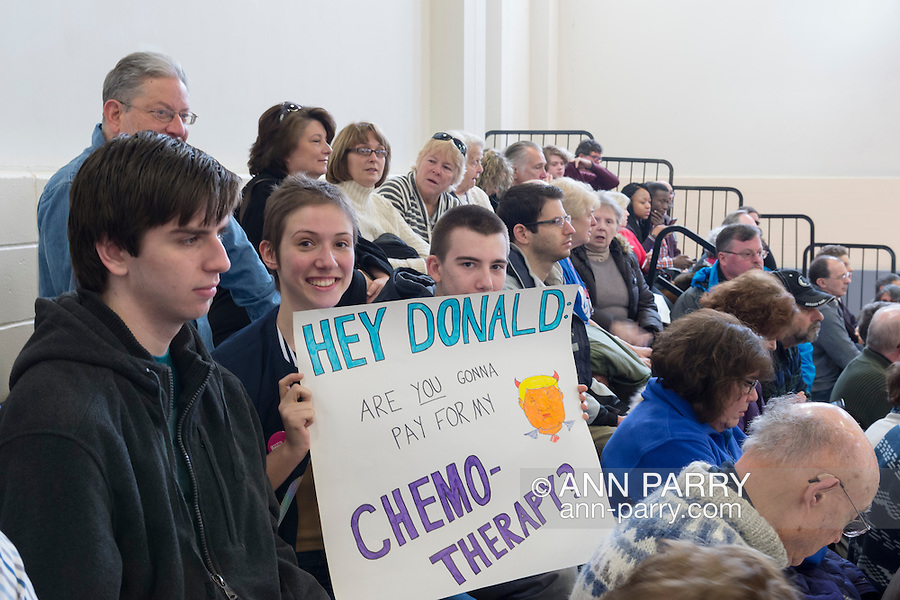 "Westbury, New York, USA. January 15, 2017.  BRIDGIT SQUITIRE, of West Islips holds a sign asking ""HEY DONALD, ARE YOU GONNA PAY FOR MY CHEMO-THERAPY?""  at the ""Our First Stand"" Rally against Republicans repealing the Affordable Care Act, ACA, taking millions of people off health insurance, making massive cuts to Medicaid, and defunding Planned Parenthood. Hosts were Reps. K. Rice (Democrat - 4th Congressional District) and T. Suozzi (Dem. - 3rd Congress. Dist.). It was one of dozens of Bernie Sanders' rallies nationwide for health care that Sunday."