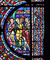 An angel and 3 apostles to the right of the scene of Jesus, flanked by 2 angels, collecting the soul of Mary depicted as a naked child, to take her to heaven, or the Elevation of the Soul, from the Glorification of the Virgin stained glass window, in the nave of Chartres Cathedral, Eure-et-Loir, France. This window depicts the end of the Virgin's life on earth, her dormition and assumption, as told in the apocryphal text the Golden Legend of 1260. Chartres cathedral was built 1194-1250 and is a fine example of Gothic architecture. Most of its windows date from 1205-40 although a few earlier 12th century examples are also intact. It was declared a UNESCO World Heritage Site in 1979. Picture by Manuel Cohen